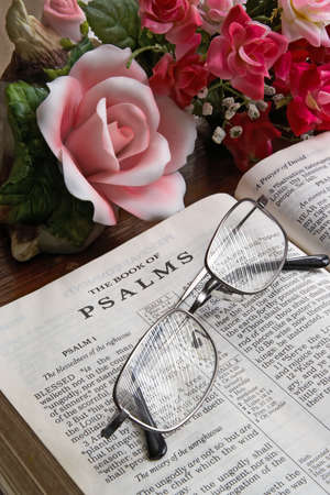 An open Bible turned to Psalms on a table with reading glasses. photo