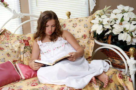 A ten year old girl reading the Bible in bed.