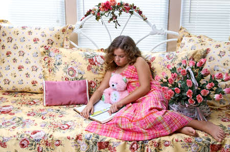 A young girl with her teddy bear, reading the Bible.