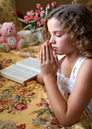 bible reading: A young girl saying her bedtime prayers.