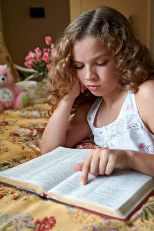 A young girl reading her Bible before going to bed. 版權商用圖片