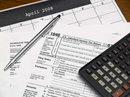 taxable: Income tax forms with a pen and calculator on a table. Stock Photo