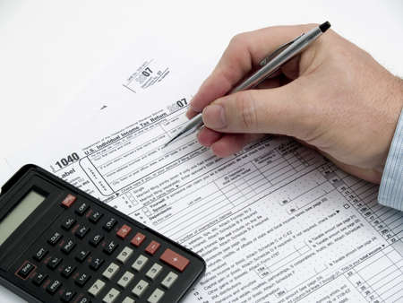 A hand holding a pen filling out tax forms.