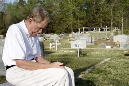 lamentation: Un vecchio uomo seduto nel cimitero.  Archivio Fotografico