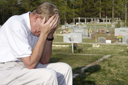 grieve: An older man sitting in the cemetery.