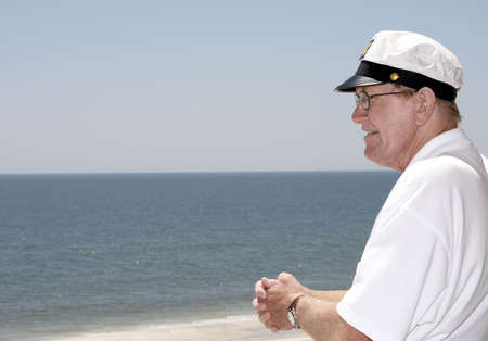 An old man looking out at the sea. Imagens