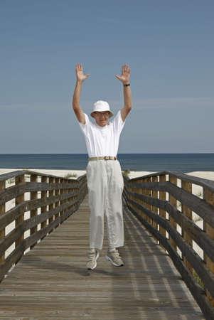 An older man jumping for joy at the beach. 版權商用圖片
