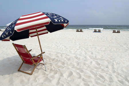 stripe: A red, white and blue beach chair and umbrella on the beach. Stock Photo