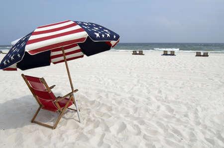 Een rood, wit en blauw strand stoel en parasol op het strand. Stockfoto