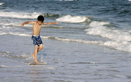 A young boy on a skimboard.