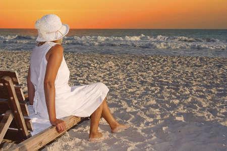 strandstoel: Een vrouw zit op een houten stoel op het strand. Stockfoto