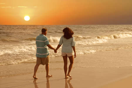 A couple walking together on the beach at sunset.