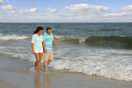 A couple walking together on the beach.