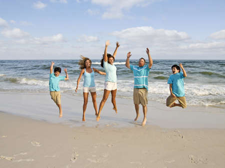 A family of five jumping on the beach.