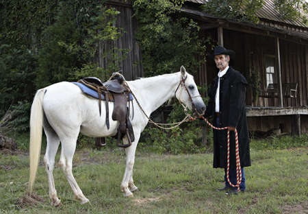A cowboy standing with his horse.