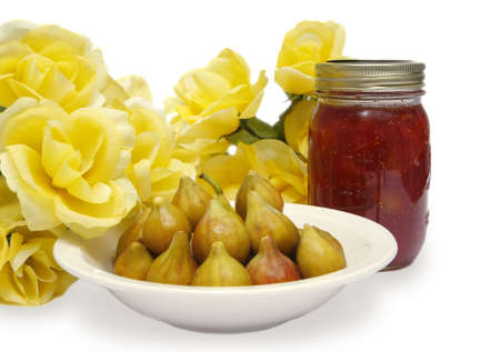 A bowl of fresh figs with a jar of preserves.