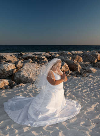 A bride kneeling and praying on the beach.