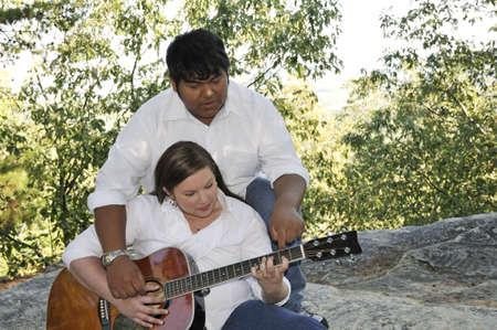 A boy teaching his girlfriend to play the guitar. Reklamní fotografie