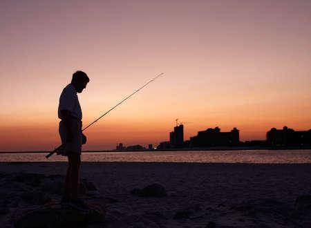 A fisherman near the end of a day at the Alabama gulf coast. 版權商用圖片