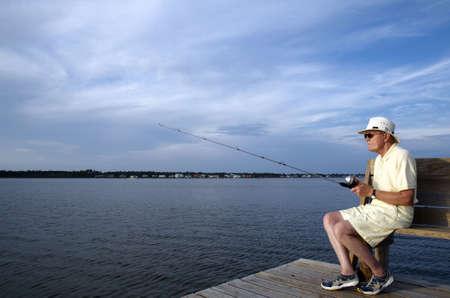 hombre pescando: Un hombre superior de pesca desde el muelle por s� solo. Foto de archivo