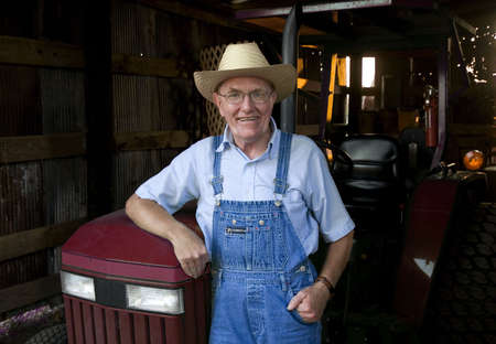 A farmer standing in front of his tractor in the barn. Фото со стока - 6743352