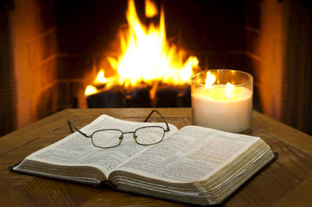 An open Bible on a table in with a fireplace in the background. photo