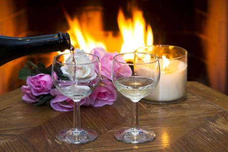 White wine being poured into on of two glasses in front of a fireplace.