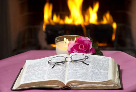 An open Bible on a table in with a fireplace in the background. 版權商用圖片