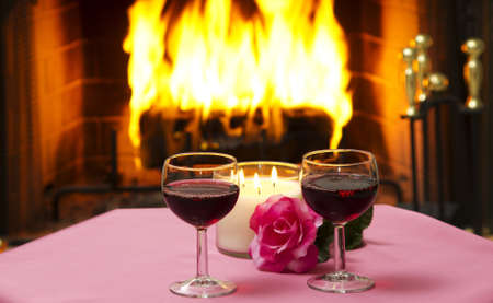 Two glasses of wine on a table with a fireplace in the background.