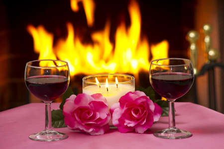 Two glasses of wine on a table with a fireplace in the background. photo