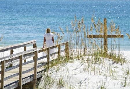 A lady standing beside a cross at the beach. 版權商用圖片