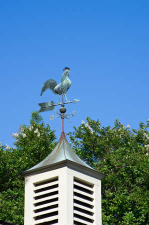 An old weather vane on a roof top. photo