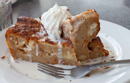 Homemade bread pudding in rum sauce on a saucer.