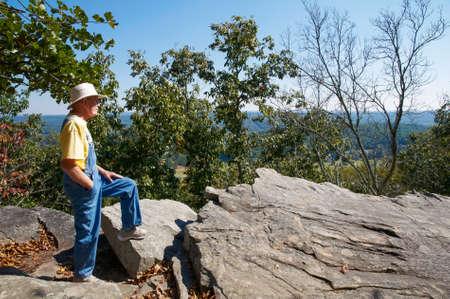 A senior man enjoying the view from a mountain top  版權商用圖片