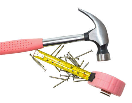 Ladies pink hammer, nails and a measuring tape on a white background