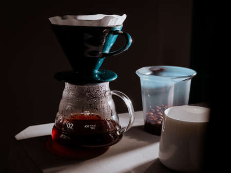 Fresh filtered coffee in glass cup on black background.