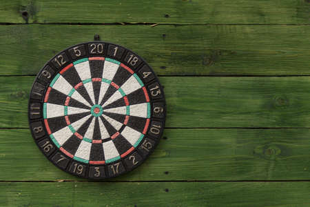 holed: Dart board on a green wooden wall