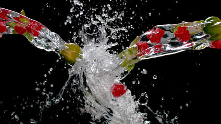 Fruits in the streams of water from both sides merge with splashes on a black background Banco de Imagens