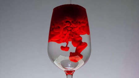 Addition of liquid red dye in a glass of water, which when dissolved takes on unusual forms
