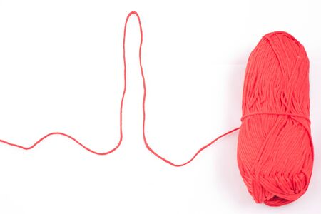 Cardiogram shaped thread and red skein on white background