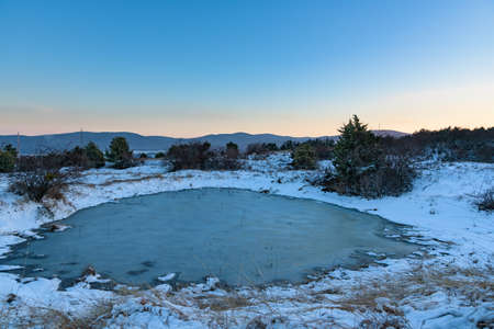 Winter sunset landscape with frozen lake