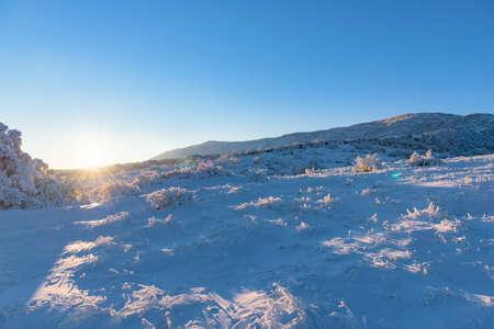 Sun hides behind the frozen mountain, winter mountainscape Stock Photo