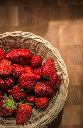 The Red Ripe Strawberries in Wicker Basket on Wooden Desk.