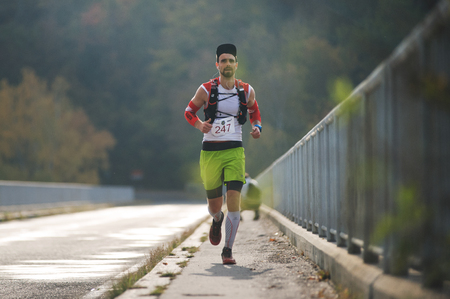 CZECH REPUBLIC, SLAPY, October 2018: Trail Maniacs Run Competition. Man Running Across the Bridge. Low Depth of the Field and Backlight. 新聞圖片