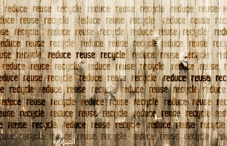 Text Reduce Reuse Recycle burned into Wooden Background.