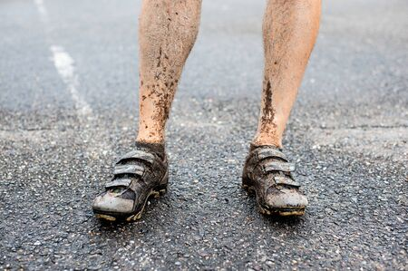 Detail of mans legs in cycling spikes after ride in wet and muddy terrain. Фото со стока
