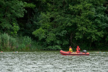 Degenbachsee, Germany, 28. July 2019. Water Rescuer on a Motorboat Watching Swimming People during Ilshofen Triathlon. Редакционное