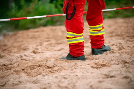 Legs of rescuer standind on the sand in front of red and white tape. Red trousers with reflective elements.