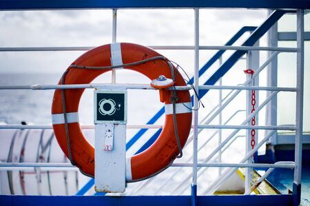 Red and white lifebuoy hanging on railing of ferry.