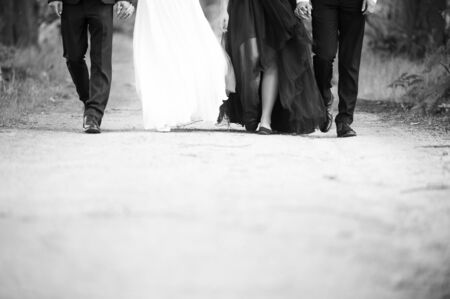 Legs of groom, bride and bridemaid and bestman. Black and white photo. Фото со стока